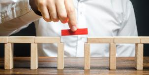 Photo of someone placing a block in a toy bridge