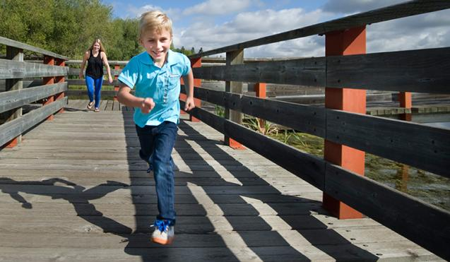 Photo of young boy running down the boardwalk on Telford Lake