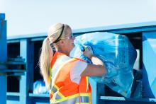 Eco Station employee with blue bag recyclables